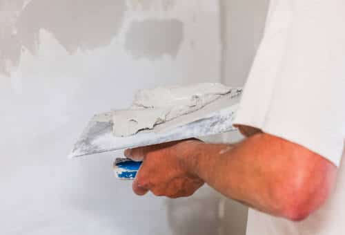 person patching up holes in drywall